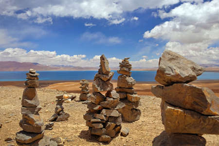 Stone formations at the Pekutso Lake, in Tibet, against a blue sky covered by white clouds.