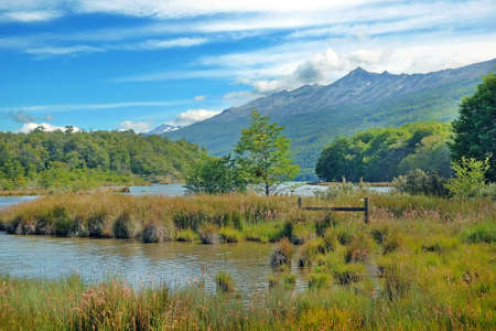 Panoramic view of Tierra del Fuego National Park, showing mountains surrounded by green vegetation and water, against a blue sky.