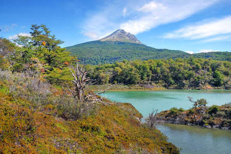 Panoramic view of Tierra del Fuego National Park, showing a volcano surrounded by green vegetation and water, against a blue sky. Stock Photo