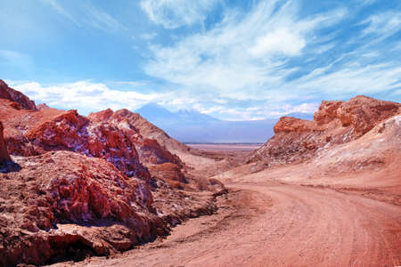 Panoramic view of road in the Moon Valley in red and orange colors near San Pedro de Atacama, in Los Flamencos National Reserve in the northern part of Chile, against a blue afternoon sky covered by clouds.