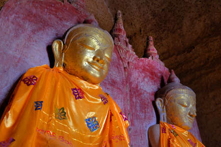 Ancient Buddha statues in a temple in old Bagan, Myanmar, covered in orange textiles with colorful motifs.