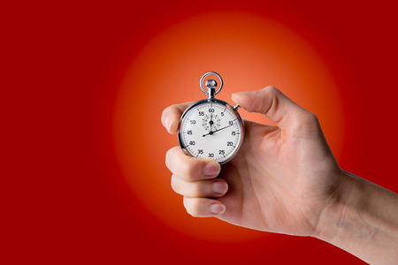 stop watch: timer hold in hand, pressed button - red background