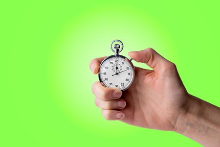 timer hold in hand, pressed button - green background Reklamní fotografie