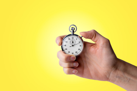 Tiempo: asimiento temporizador en la mano, botón presionado - fondo amarillo