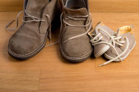 Closeup of fathers shoes close to childs shoes on parquet Reklamní fotografie