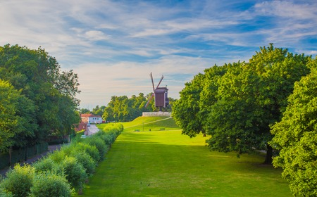 Sunny summer evening in Brugge. Bruges cityscape with old windmill. Park in Bruges with green grass and trees.
