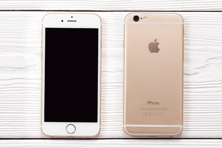 New York, USA - March 27, 2018: Iphone smartphone front and back side on wooden background. Iphone with black blanck screen top view. Editorial