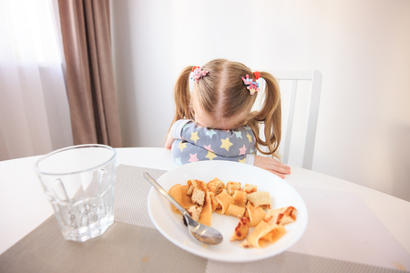 Girl doesn't want eat her dinner. Theme of problems with children feed. Standard-Bild