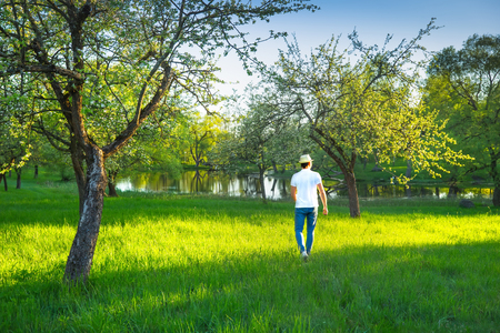 Attractive young man in natural parkland in summer morning enjoying sunlight. Man in summer clothes outdoors.