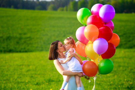 Young woman with kid in white dress with colorful balloons outdoors. Mom kissing daughter. Happy family enjoying fresh summer air. Stock Photo