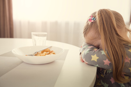 Little girl refuses to eat. Child meal difficultes theme.