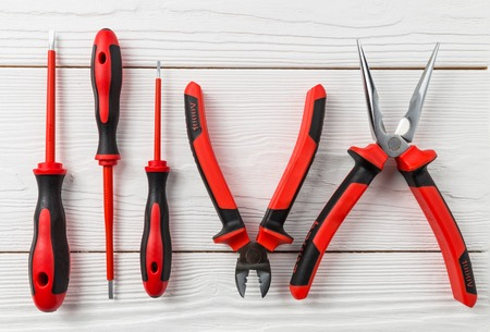 Professional electrical tools on white wooden background. New shiny tools.