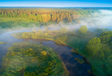 Sunny summer morning on river. Fog over meadow. Summer nature. Amazing aerial landscape.