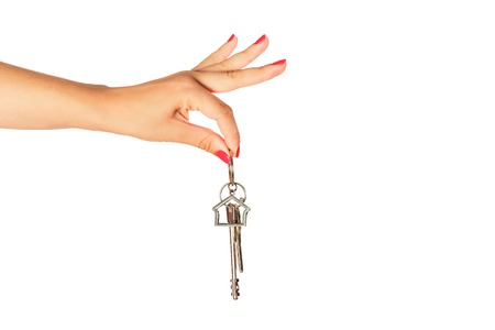 Woman hand holding keys isolated on white background. Real estate sale concept.