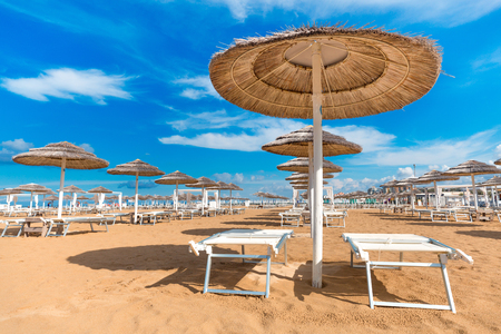 Straw sun umbrellas on beach. Rimini empty beach with chaise lounges and umbrellas. Clear blue sky background. Summer recreation. Vacation theme.