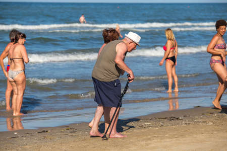Rimini, Italy - June 20, 2018: Old man with a cane walking along the beach in Rimini. Woman helps the old man walk along the sand on the seashore.