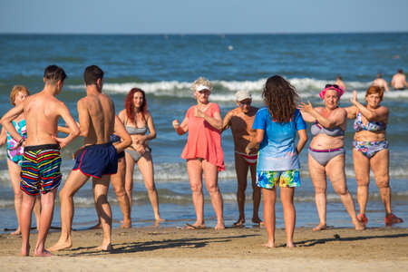Rimini, Italy - June 20, 2018: Elderly people doing wellness exercises on the beach in Rimini. Theme of health and entertainment.