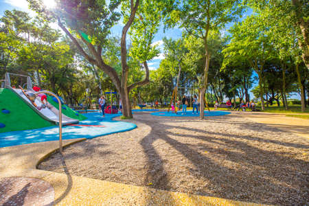 Rimini, Italy - June 14, 2018: Outdoor children playground in Rimini with green trees on a sunny day.