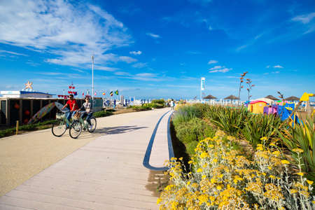 Rimini, Italy - June 14, 2018: Embankment of Rimini on a sunny day. Cyclists ride along the bicycle path along the beaches.