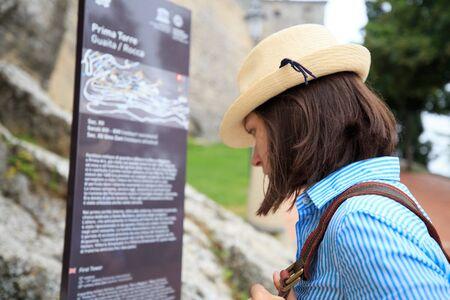 San Marino, Italy - June 14, 2018: Tourist girl reading information of San Marino fortress on information stand.