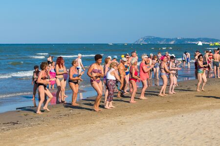 Rimini, Italy - June 20, 2018: Group of elder people on Rimini seashore enjoying sunny summer weather. Light gym exercises for old people outdoors. Editorial