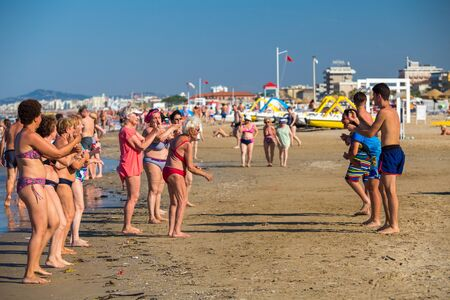 Rimini, Italy - June 13, 2018: Senior people dancing with animator on Rimini beach Editorial