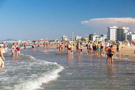 Rimini, Italy - June 13, 2018: People walking on beach in Rimini, Italy. Summer day on Rimini seashore. Editorial