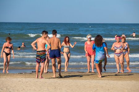 Rimini, Italy - June 13, 2018: Group of senior people dancing on summer sunny day on beach at the sea. Rimini, Italy.