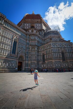 Florence, Italy - June 15, 2018: Sightseeing of Florence. Little girl jumping on The Florence Cathedral background. Beautiful destination of Italy. Florence. Editorial