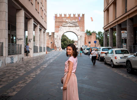 Rimini, Italy - June 11, 2018: Attractive girl on Rimini street turned to camera. Famous destination in Italy. Rimini historic center.