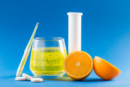 Flu medicine. Fruit Flu effervescent. Health care concept. Thermometer, pills, orange fruit, glass with medicine and white container on blue background. Фото со стока