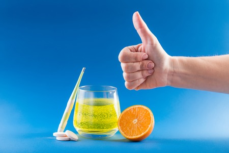 Flu cure. Fruit dissolved Flu Pills. Health care concept. Thermometer, pills, orange fruit, glass with medicine and hand with thumb up on blue background. Banco de Imagens