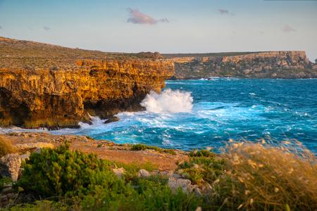 Malta coastline. Malta seascape. Rocky seashore and sea waves at sunset. Beautiful summer seascape.