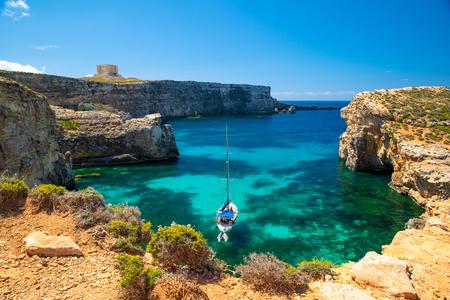 Malta resort. Crystal lagoon with yacht. Malta landscape. Comino island. Summer sunny seascape. Malta coastline.