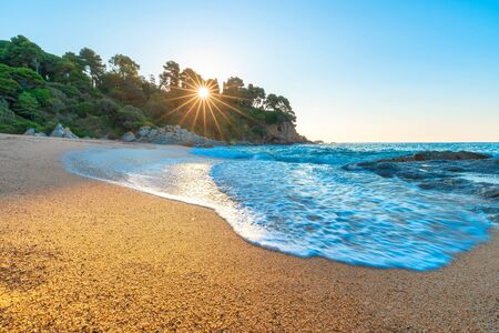 Beach and sun. Sunny tropical background. Surf on beach. Rising sun shines on clean sand and sea foam. Costa brava coast.