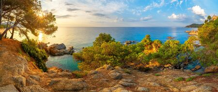 Spain, Catalonia. Costa Brava coast in the morning. Panoramic landscape with blue sea and green trees illuminated with rising sun. Lloret de Mar resort.