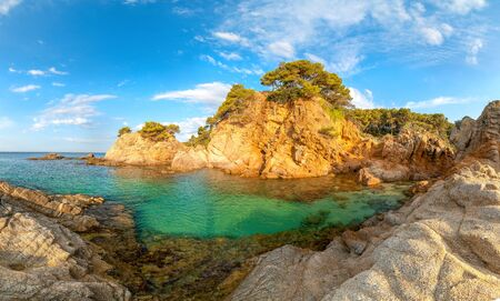 Spain, Catalonia. Typical landscape of Costa Brava. Clear sea water and cliffs with morning sunlight under blue sky. Lloret de Mar resort. Standard-Bild