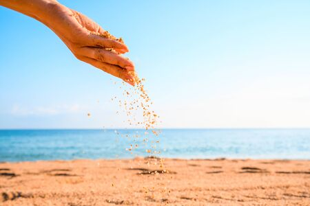 Summertime. Sand falling from woman hand. Clear blue sky and beach on the background. Vacation background with copy space. Standard-Bild