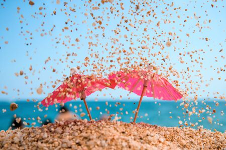 Two red coctail umbrellas under sand rain. Blue sea and sky at the background. Resort background. Фото со стока