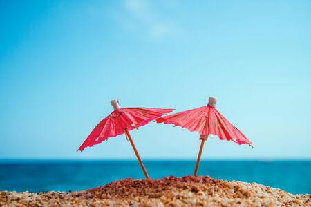 Vacation concept. Resort background. Two small red umbrellas in sand on blue sea and sky background.
