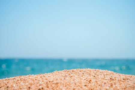 Resort background. Vacation background. Beach sand close-up with shiny blue sea backdrop. Spain, Costa Brava. Standard-Bild
