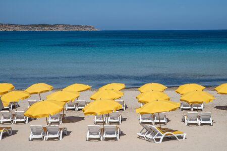 Malta. Maltese beach. Yellow sun umbrellas on beach with blue sea and sky background. Resort background.
