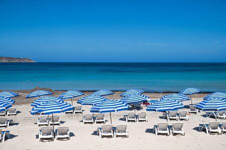 Malta. Maltese beach. Blue sun umbrellas on beach with blue sea and sky background. Resort background. Standard-Bild