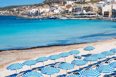 Malta. Maltese beach. Blue sun umbrellas on beach on blue sea background. Resort background.