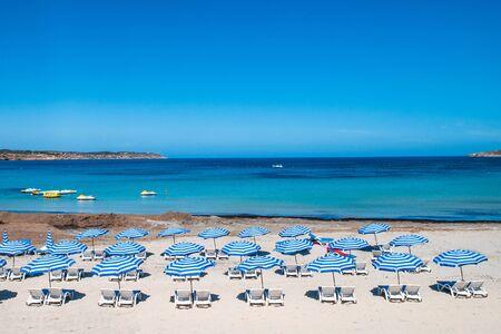 Malta. Maltese beach. Blue sun umbrellas on beach on blue sky background. Resort landscape.