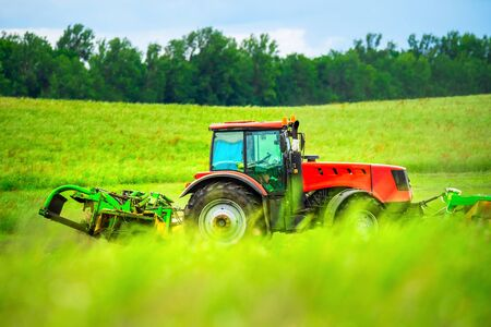 Agriculture. Red tractor working in green field. Farm industry.