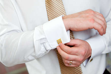 cuff links: The man clasps a cuff link on a shirt