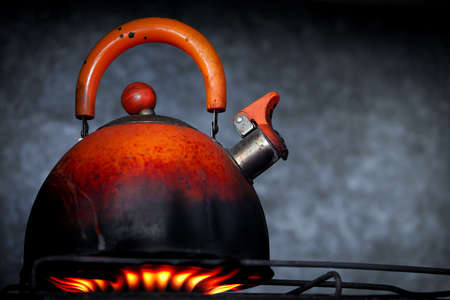 Old teapot on a gas cooker photo