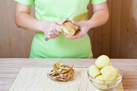 paring knife: Preparation of a potato for meal preparation Stock Photo