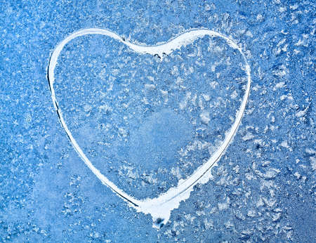 Snowflakes at a window in the form of heart photo